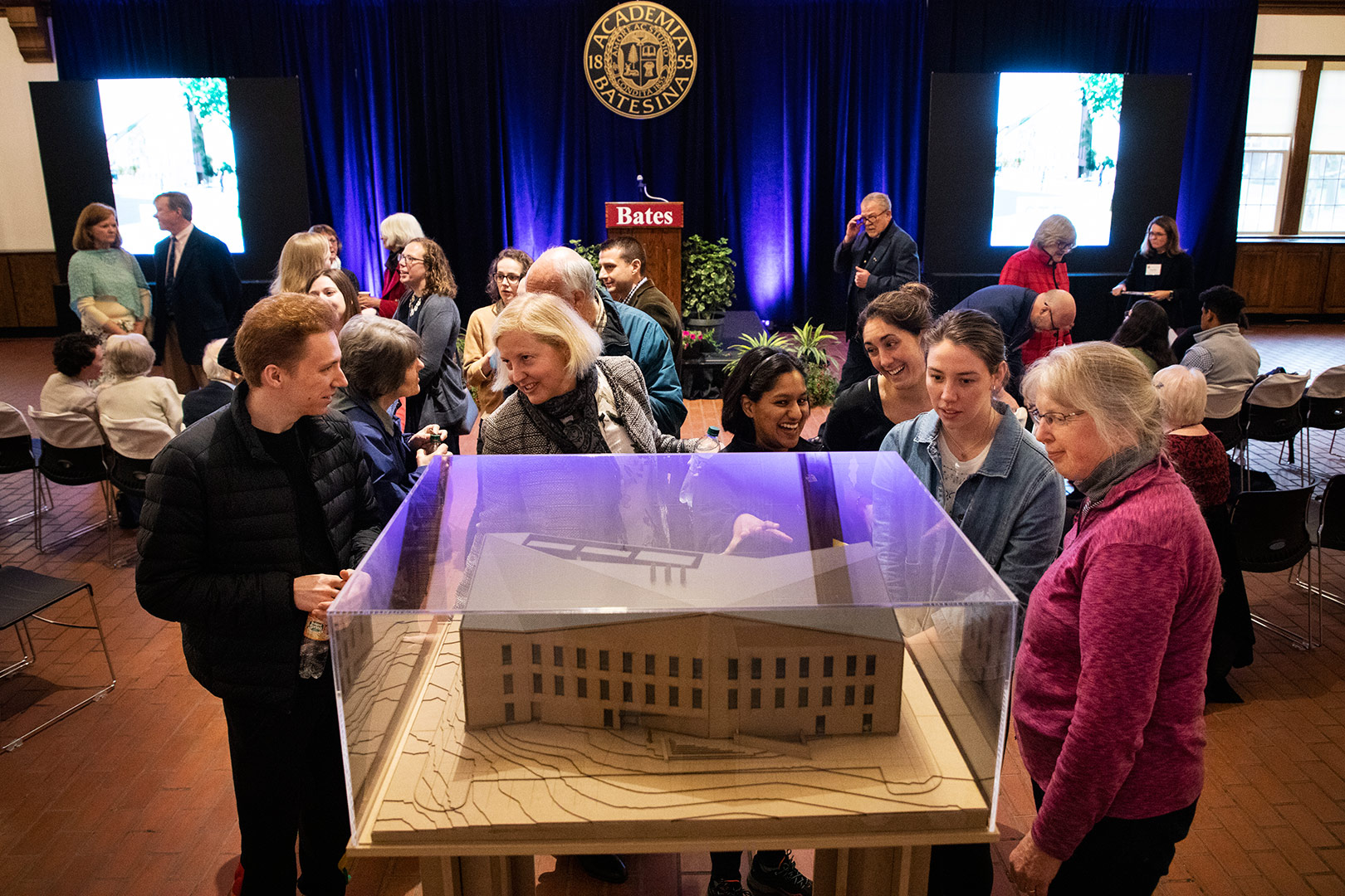 Shortly before the start of a campus-wide celebration of the groundbreaking of the Bonney Science Center on May 2, attendees inspect a model of the building in Memorial Commons. (Theophil Syslo/Bates College)
