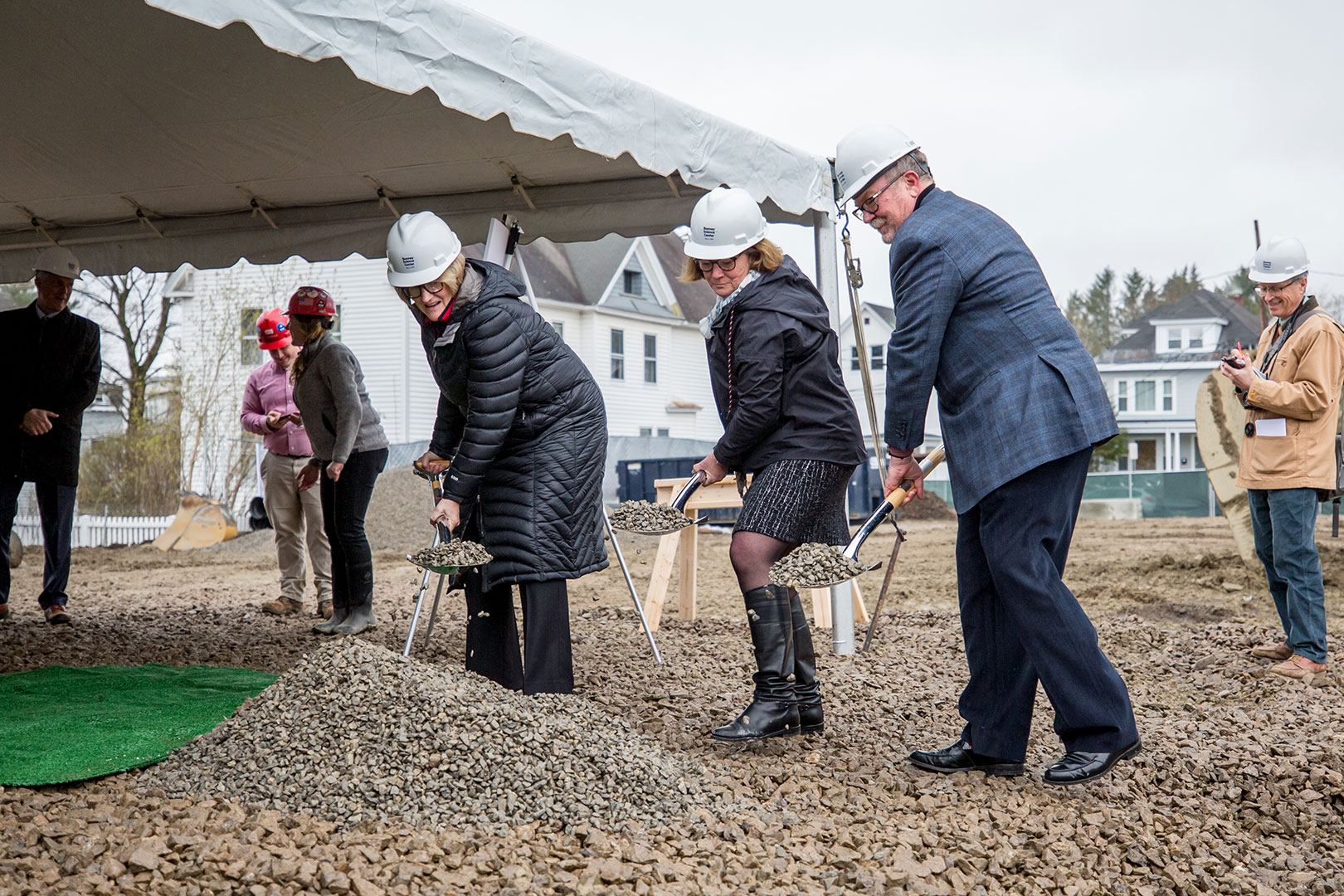 Flinging the ceremonial gravel during the groundbreaking for the Bonney Science are, from left, Bates President Clayton Spencer, Alison Grott Bonney '80, and Michael Bonney '80. At right, a passing stranger takes notes. (Rene Roy for Bates College)