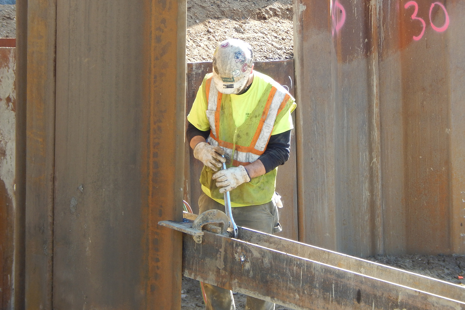 An employee of South Portland subcontractor H.B. Fleming tightens a clamp holding a sheet pile in place on May 6. (Doug Hubley/Bates College)