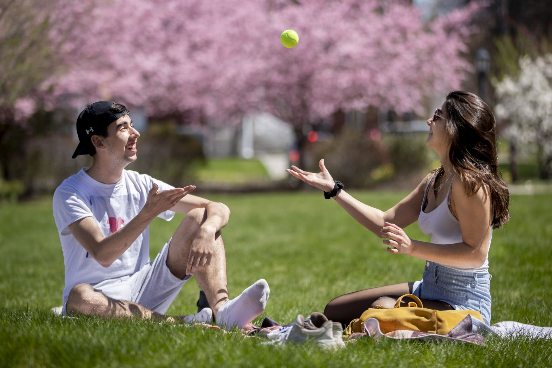 "After a week of rain, a warm and sunny day filled with the sights and sounds of spring. ""We're enjoying the first day that actually says like Short Term, says Anais Ranque '21, a double major in music and psychology from Vesenaz, Switzerland, as she tosses a tennis ball with Jake Bart '21, a psychology major from New York City. The two took to the lawn outside of of 280 College Street, where, like many of their classmates, they soaked up the Monday afternoon sun. ""It's been a long, cold winter,"" Bart said."