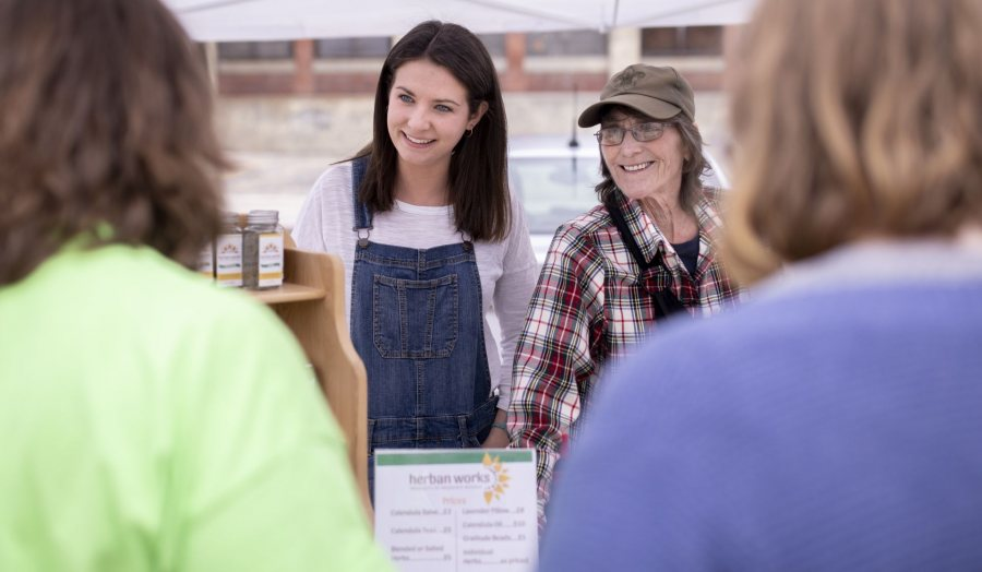 Clio Barr '19 of Hallowell, Maine, is a STA/RT (SHORT TERM ACTION/RESEARCH TEAM) partner with the Center for Wisdom's Women Herban Works. Her project title is Creating Marketing Materials and a Business Plan for Sophia's House.On the first spring day of the 2019 Lewiston Farmer's Market, Barr sells products on Sunday, May 12, with Judy Maloneygarden and production coordinator and volunteer Mary Hopkins, who also helps with harvesting and planting.
