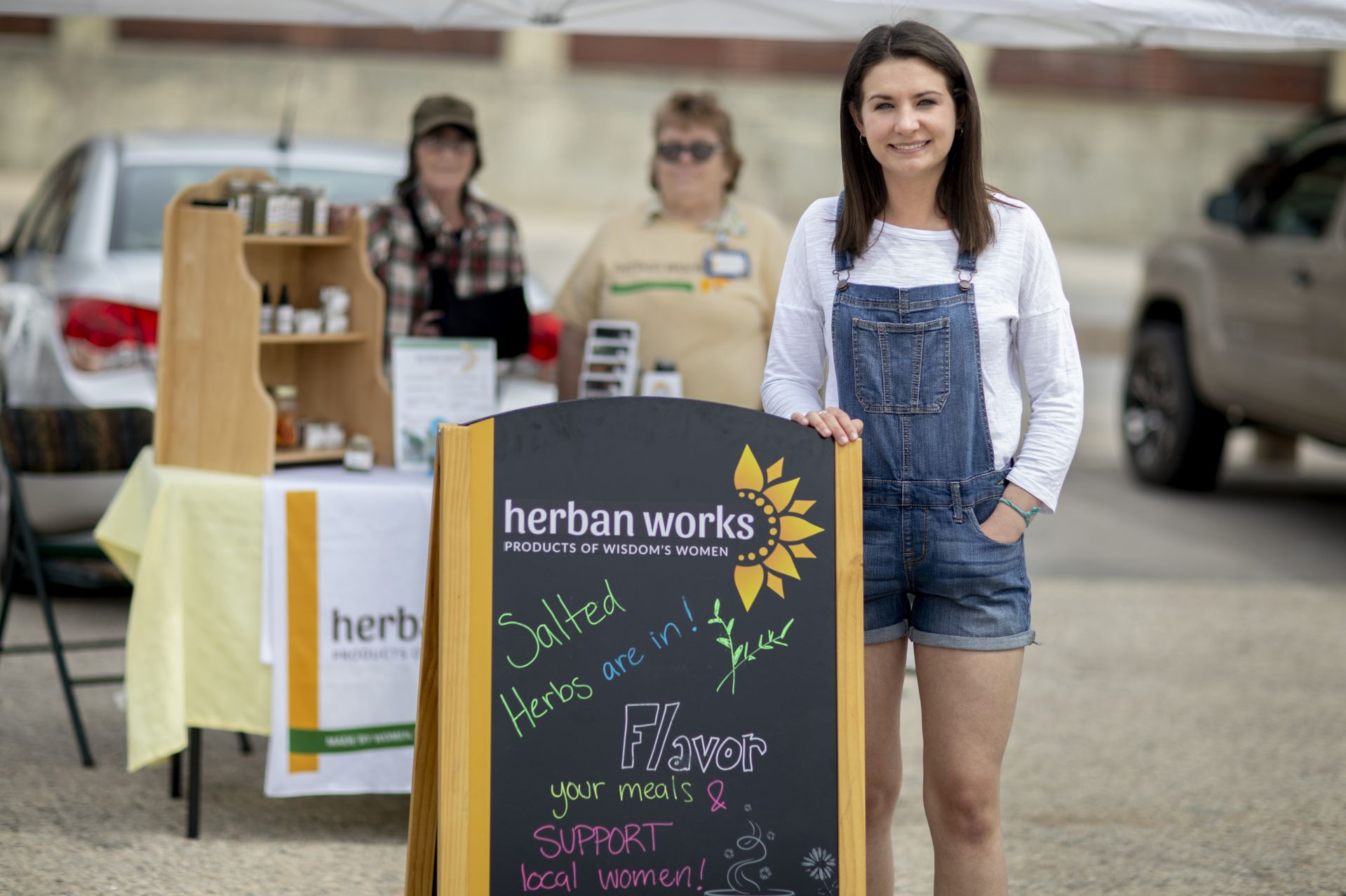 Clio Barr '19 of Hallowell, Maine, is a STA/RT (SHORT TERM ACTION/RESEARCH TEAM) partner with the Center for Wisdom's Women Herban Works. Her project title is Creating Marketing Materials and a Business Plan for Sophia's House.On the first spring day of the 2019 Lewiston Farmer's Market, Barr sells products on Sunday, May 12, with Judy Maloney garden and production coordinator and volunteer Mary Hopkins, who also helps with harvesting and planting.