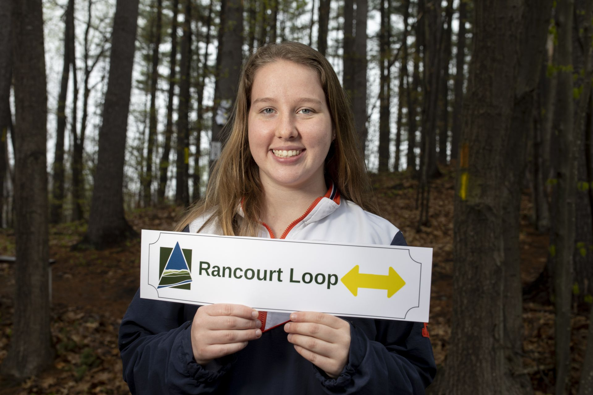 "Katherine ""Katie"" Ennis of Morristown, N.J. '20 is partnering with the Androscoggin Land Trust to advance trail signage and mapping improvements. She's helping them assess trail conditions and supporting their efforts to develop a comprehensive trail improvement plan. Helping to create maps and signage templates, researching practices for trail management among other trail managing organizations, developing a plan for how the work on the trails can be completed.Katie, in red, white, and blue jacket, is shown at the entrance and just inside of the Androscoggin Land Trust David Rancourt Preserve on Two Tall Pines Road, with her friend Julie Vallario, Mark Johnson, Androscoggin Land Trust David Rancourt Preserve Steward, and Shelley Kruszewski, executive director of the Androscoggin Land Trust. She brought Julie, a lifelong friend, to help her post temporary trail signs with a ladder. The permanent ones will be posted next week. STA/RT, that is — the Short Term Action/Research Team, a working group comprising 10 students who head downtown every year for five-week projects with local partners. With support from the Harward Center for Community Partnerships, the students bring skills, stick-to-itiveness, and, it turns out, a good dose of self-awareness to their work."