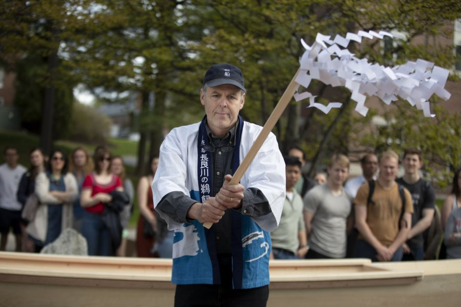Douglas Brooks shakes the streamers over the boats. (Phyllis Graber Jensen/Bates College)