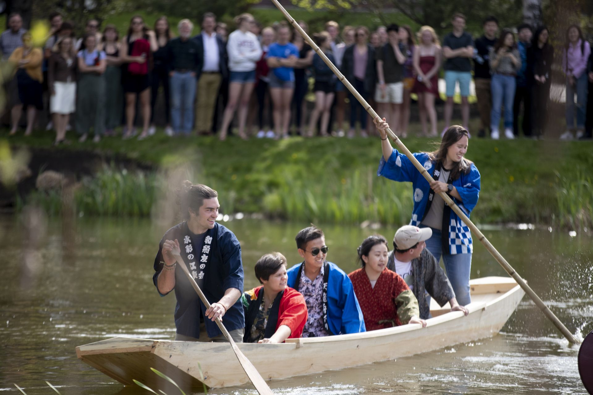 Students turn their boat in front of the crowd gathered on the shore of Lake Andrews. (Phylis Graber Jensen/Bates College)