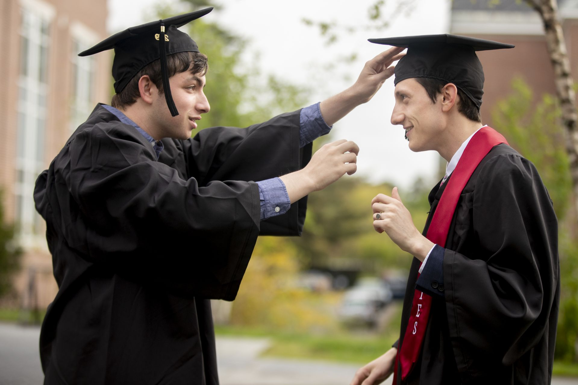 The first seniors on Alumni Walk on Commencement Day, David Unterberger (left) and Nicholas Damianos check each other's cap alignment. (Phyllis Graber Jensen/Bates College)
