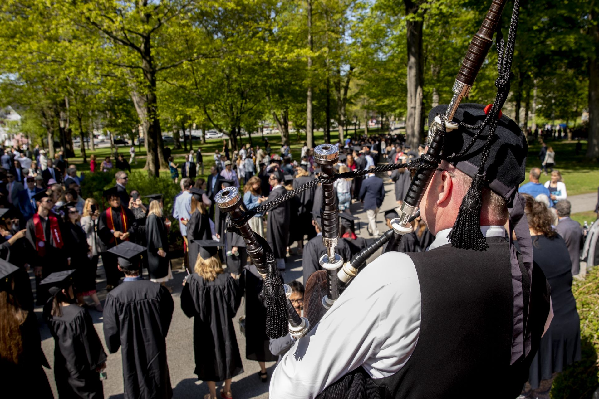 Bates College 2019 Commencement (the one hundred and fifty-third) on the Historic Quad, at which Travis Mills receives an Doctor of Humane Letter. Placing the collar on Mills is the college's mace bearer, Charles Franklin Phillips Professor of EconomicsMichael Murray.Piper Tom Ryan on the steps of Hathorn plays during the processional on Alumni Walk where students have lined up.