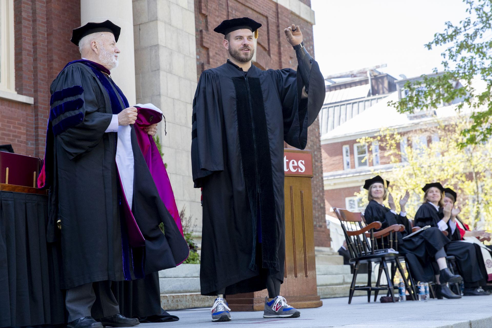 Travis Mills, a soldier injured in combat who is now an advocate for other combat veterans, receives an honorary Doctor of Humane Letters degree. Placing the collar on Mills is the college's mace bearer, Phillips Professor of Economics Michael Murray. (Phyllis Graber Jensen/Bates College)