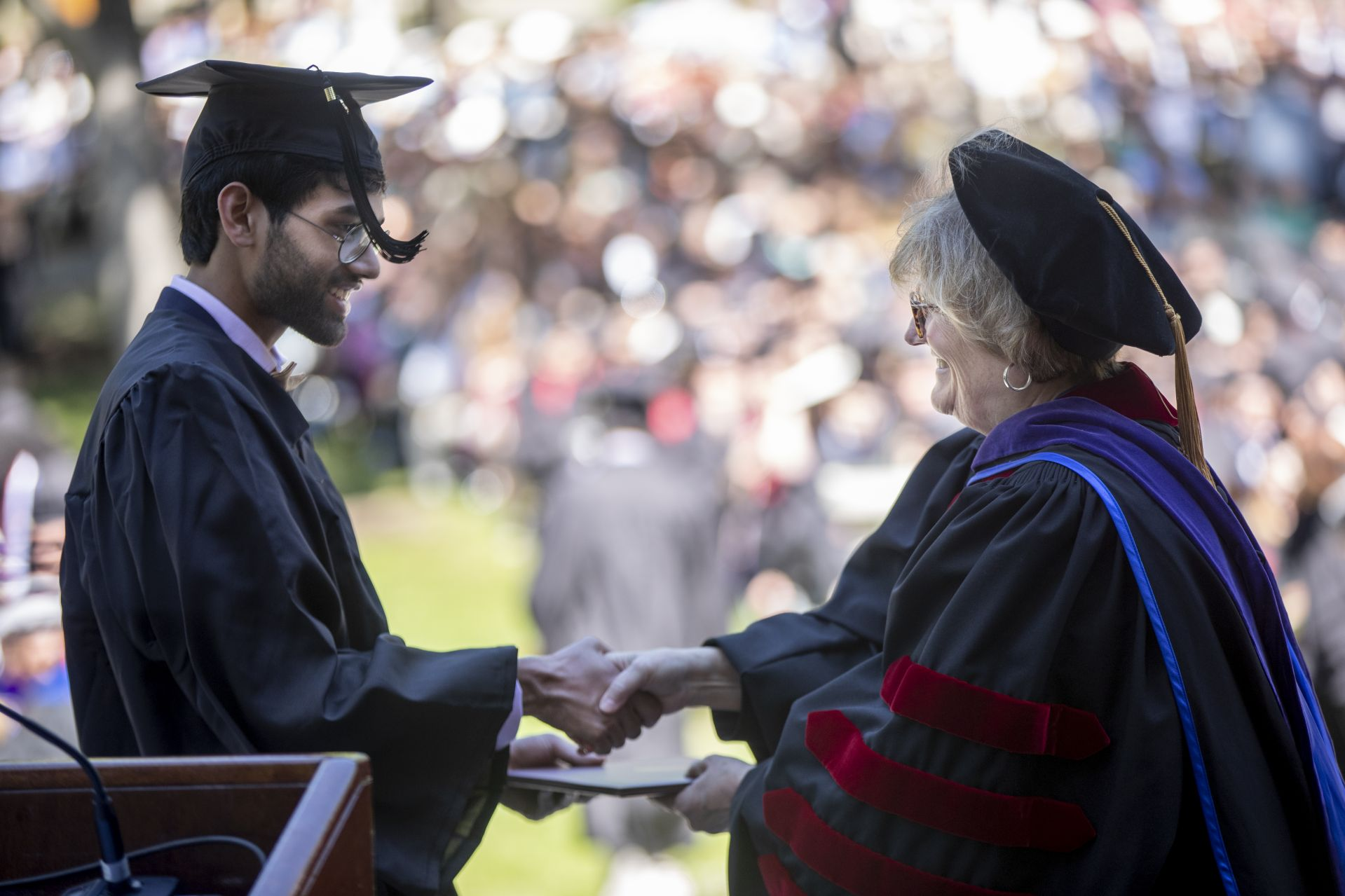 Rohan Bhat, a double major in philosophy and in classical and medieval studies, accepts his diploma from President Clayton Spencer. (Phyllis Graber Jensen/Bates College)