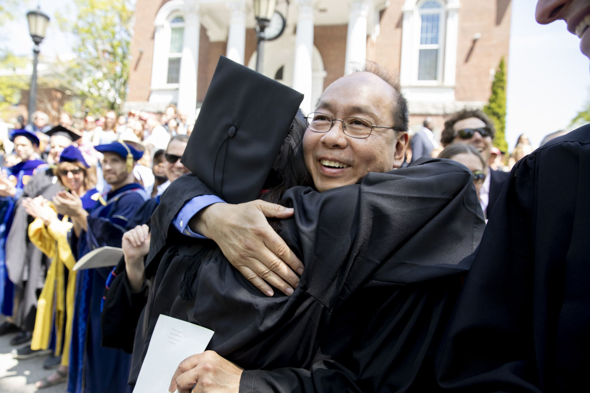 Math professor Peter Wong hugs a new graduate during the recessional. (Phyllis Graber Jensen/Bates College)