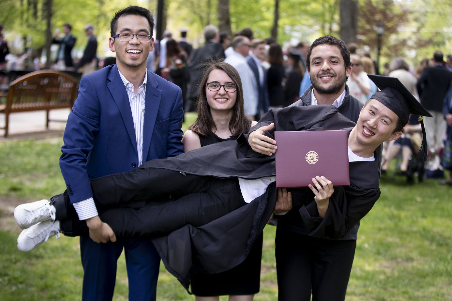 Max Huang '19, who graduated summa cum laude as a triple major in math, economics and physics, is held up by (from left) Deepsing Syangtan, Maria-Anna Chrysovergi, and Salim Ourari, all '18. (Phyllis Graber Jensen/Bates College)