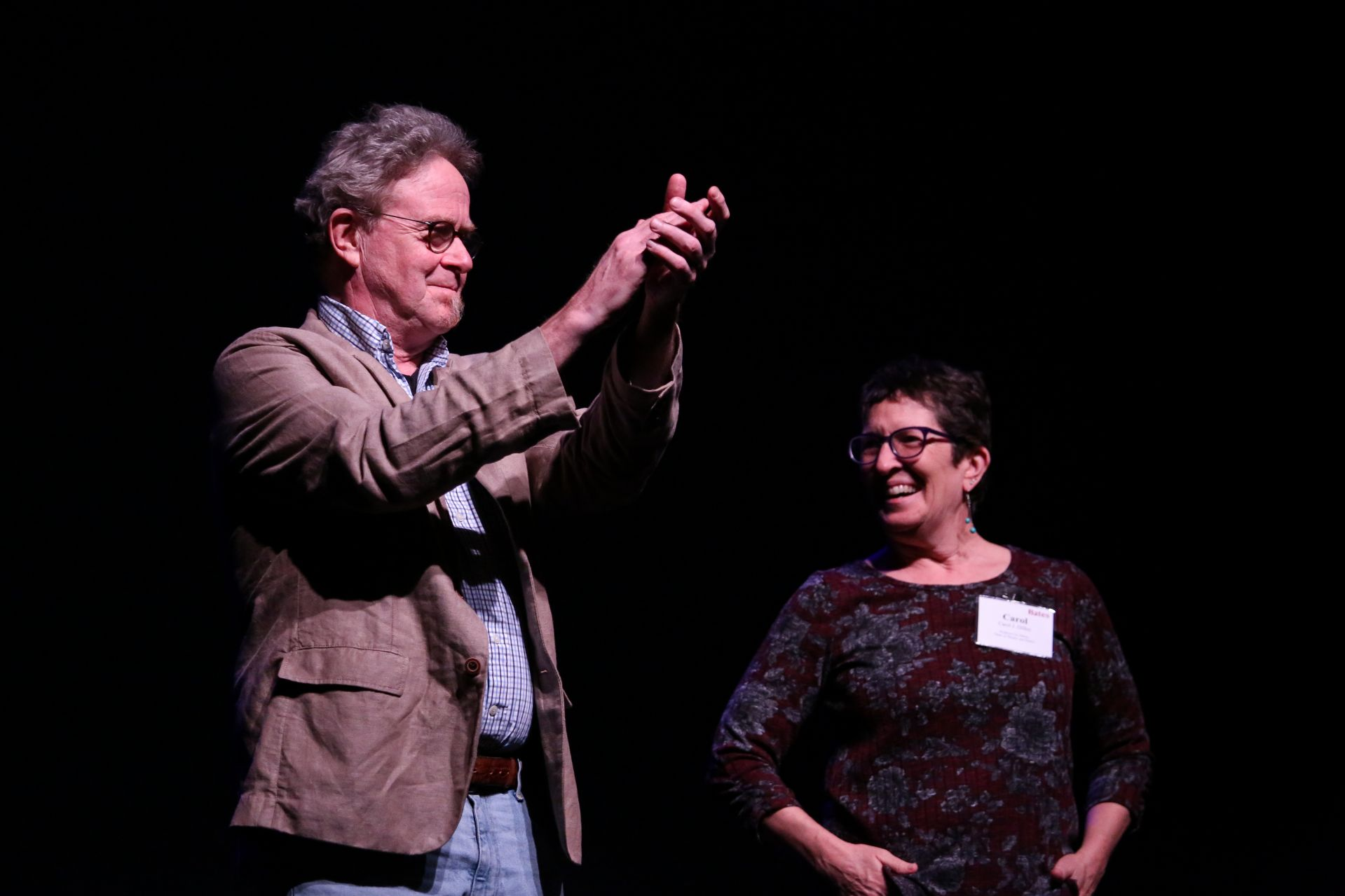 """A longtime composer for Bates dance, Alice Swanson Esty Professor of Music Bill Matthews (left) joins applause alongside Carol Dilley following the performance of """"Passing.""""(Samuel Mironko '21 for Bates College)"""