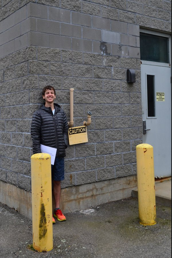 """A member of the """"In Search of Higher Ground"""" class, Henry Colt '19 poses at the wastewater treatment plant by the sea in Boothbay Harbor, Maine. Six feet tall, Colt marks the level sea water could reach during a northeaster in the year 2060 according to one scenario. (Lynne Lewis/Bates College)"""