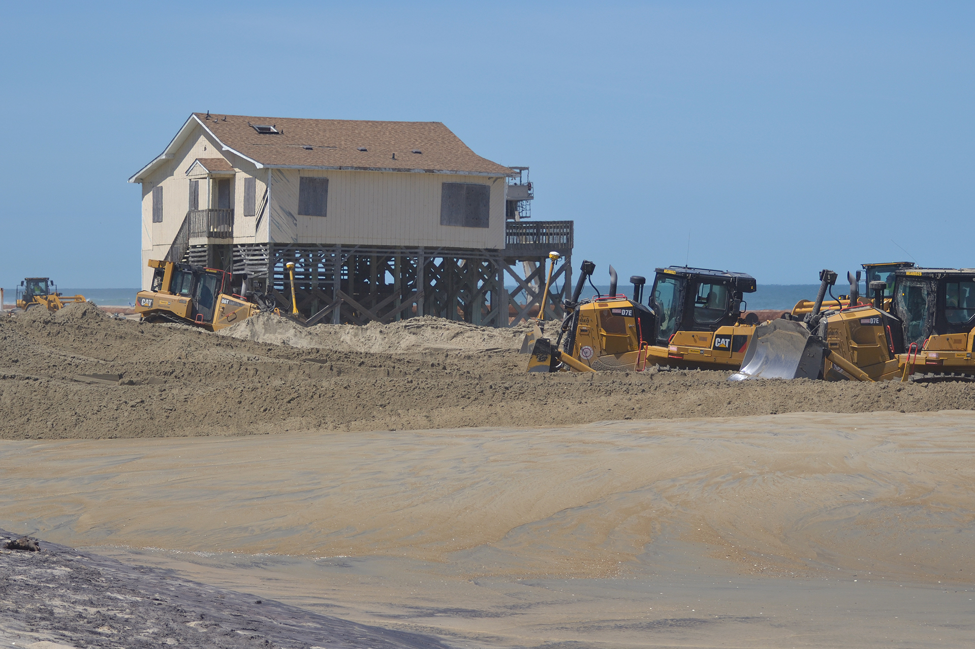 "Bulldozers spread sand near a beach house at Nags Head, N.C., part of a $43 million beach ""renourishment"" project. Sand is dredged from the ocean floor and pumped more than a mile from an offshore ""borrow"" site to the beach. (Lynne Lewis for Bates College)"