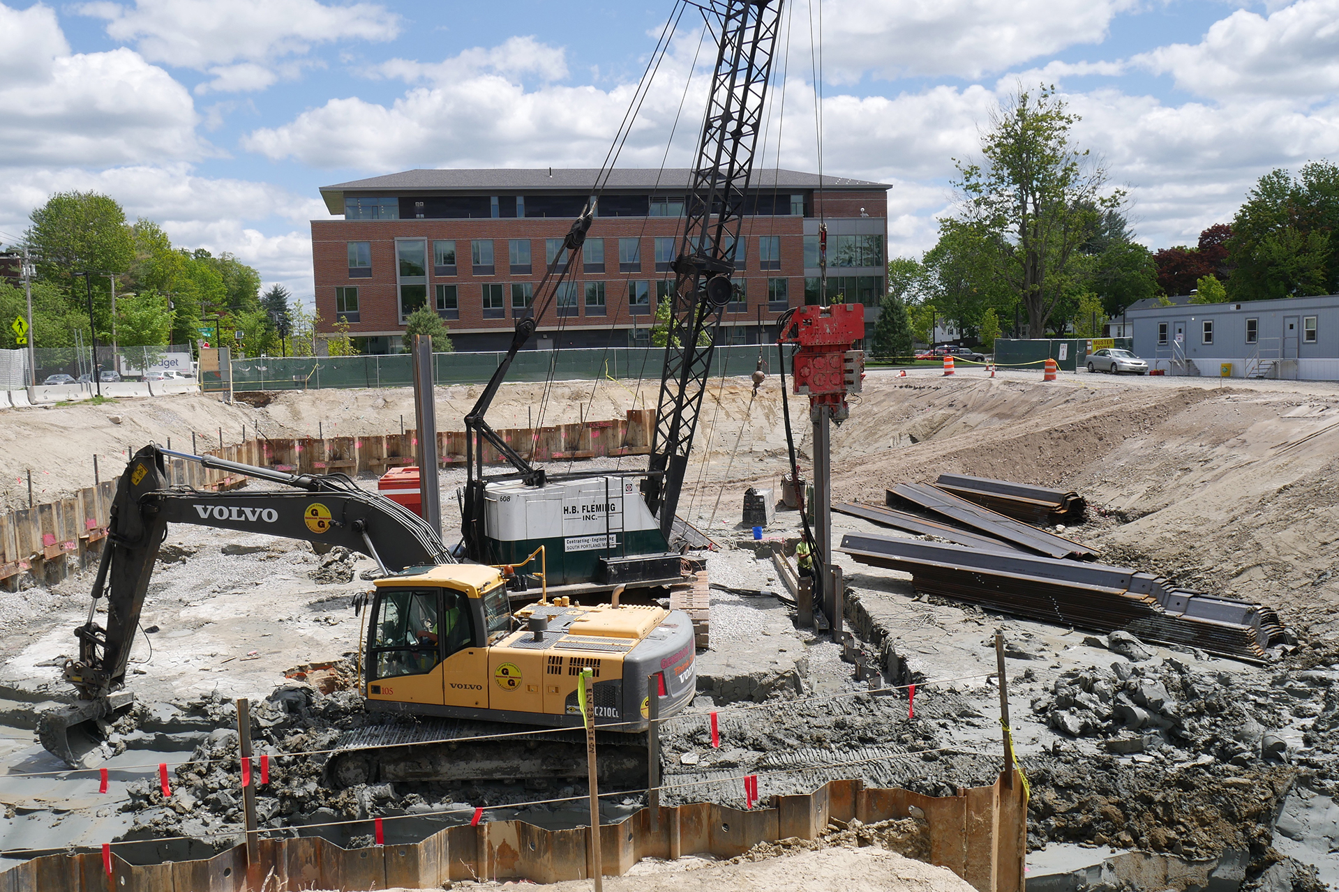 It's full-tilt action in the science building foundation hole on June 4. Suspended from the Fleming Inc. crane, the red vibro hammer is driving a sheet pile at a secondary excavation. Meanwhile, the yellow power shovel is removing clay that it will dump in a heap, not to be confused with a pile, for a second machine to load into a truck. (Doug Hubley/Bates College)