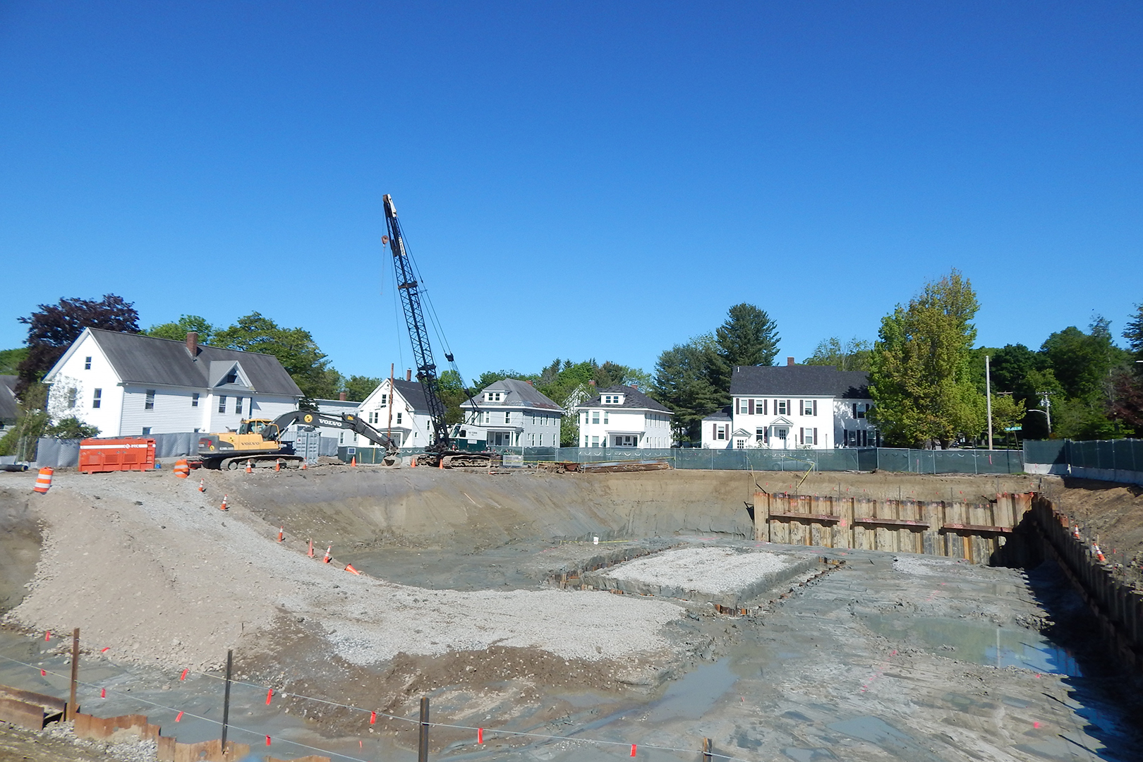 The construction site is quiet at mid-morning on June 7, the Friday of Reunion 2019. Note the tops of the sheet piles barely visible around the rectangle in the foundation hole: That spot will be dug down another eight feet or so. (Doug Hubley/Bates College)