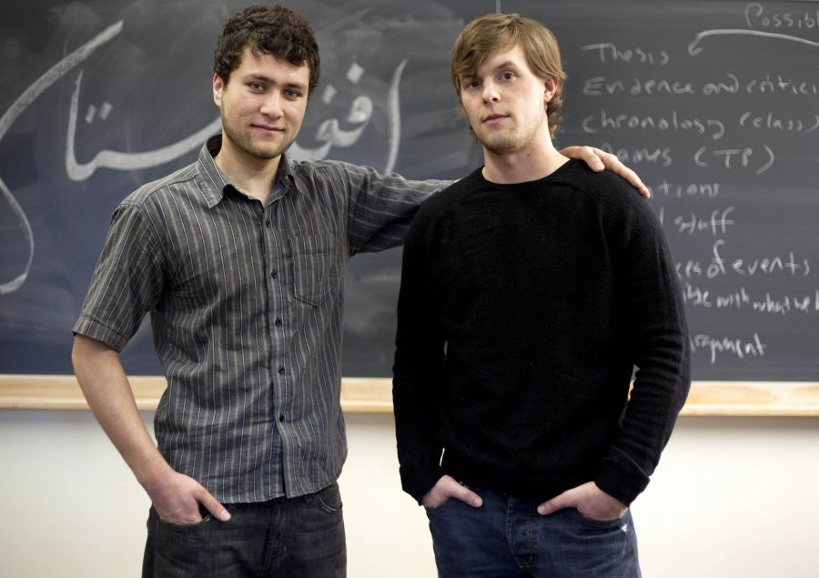 "From left, friends Mohammed Mustafa Basij-Rasikh '12 and Jared Golden '11 pose together in a Pettengill history classroom. Mustafa has written the the longer word ""Afghanistan"" (at top) and the shorter word ""peace"" (directly between their necks) in Farsi on the blackboard behind them. In some frames, ""peace"" is obscured."