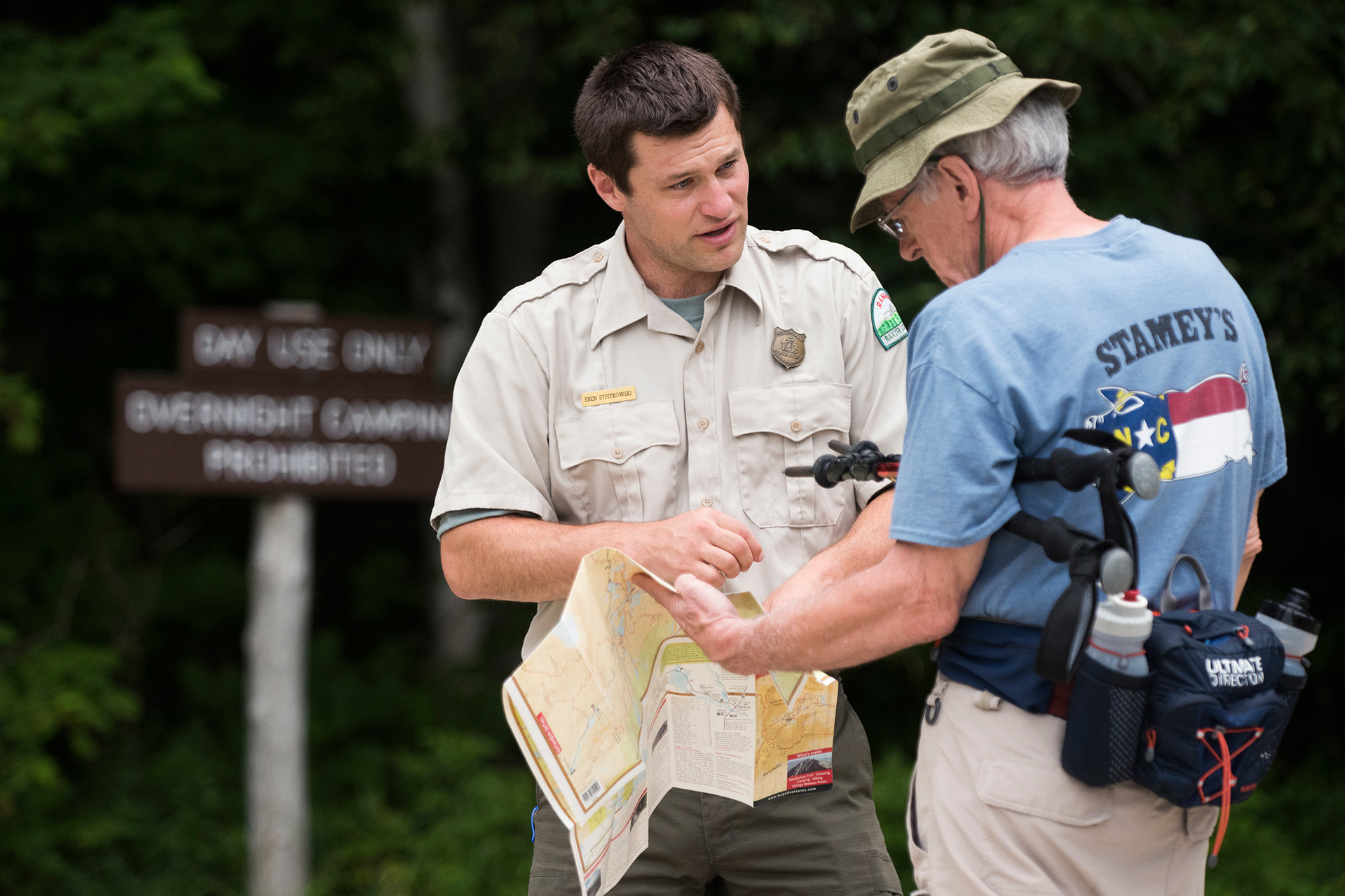 Baxter State Park, Maine—08-03-2018— Eben Sypitlowski helps park visitor Tom Fegley of Germantown Maryland at Abol Stream parking lot on Friday. Fegley is a first time visitor and was asking about a washed out bridge close by.Kevin Bennett Photo