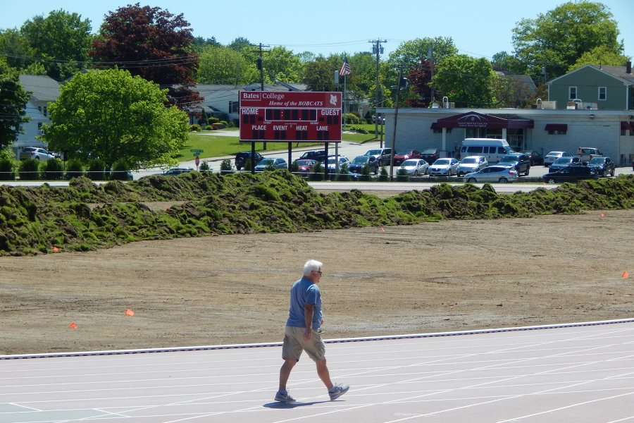 With a walker on the Russell Street track in the foreground, heaps of old sod on the Bates soccer field are awaiting removal on on June 12. (Doug Hubley/Bates College)