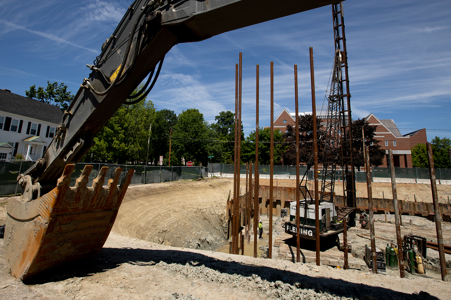 Framed by the arm of an excavator, pipe piles stand tall in the Bonney Science Center foundation hole on June 24, 2019. (Phyllis Graber Jensen/Bates College)