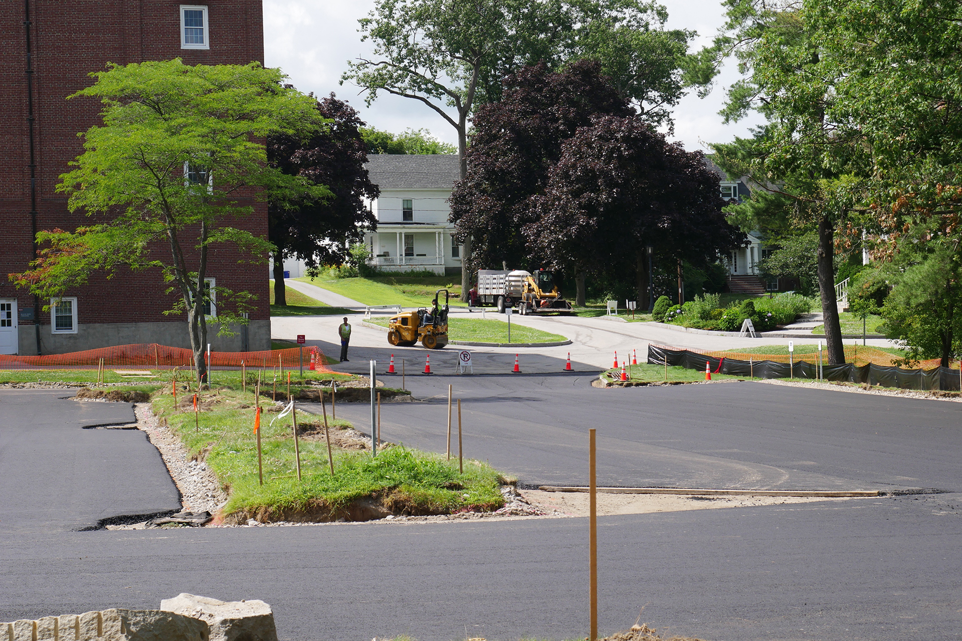 "Rolling the binder coat on the ""Pit,"" the Lane Hall parking lot, on July 17. (Doug Hubley/Bates College)"