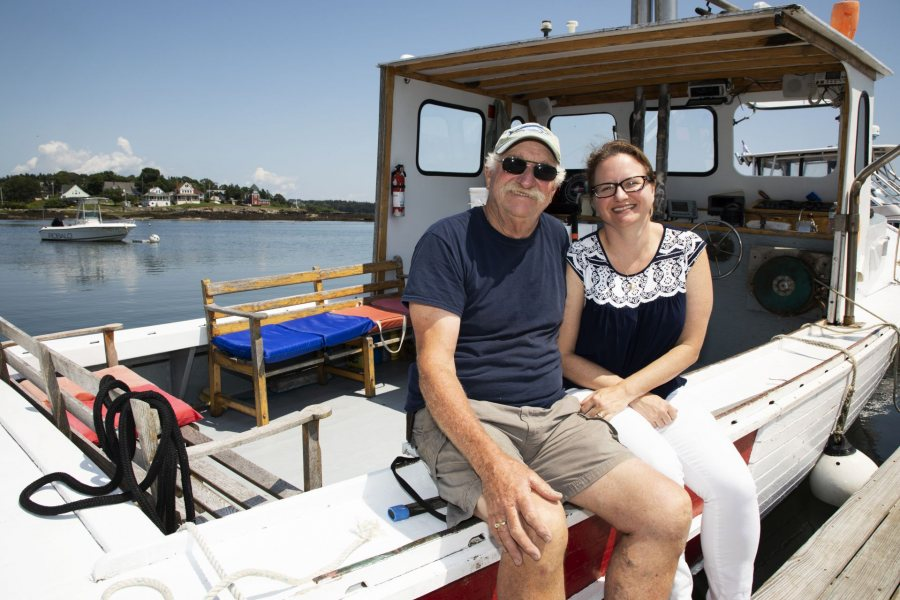 Kate McGowen Wing, '01, and her father Captain Jay McGowen, West Wind Lobster Tours in Bailey Island, pose for a portrait in between tours on July 26, 2019. Captain Jay leads a sports fishing tour in the morning and switches over to lobster tours in the afternoon, during this transition, his daughter Kate McGowen Wing brought him a sandwich for lunch. Kate works behind the scenes helping her father organize and manage all of the tourism.