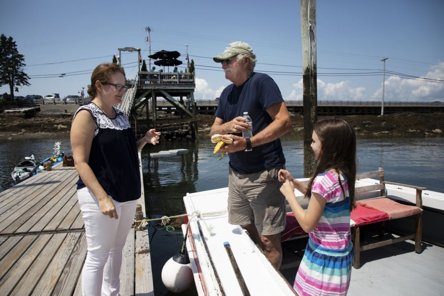 Kate McGowen Wing, '01, and her father Captain Jay McGowen, and daughter Tessa Wing, 8, of West Wind Lobster Tours in Bailey Island, interact in between tours on July 26, 2019.