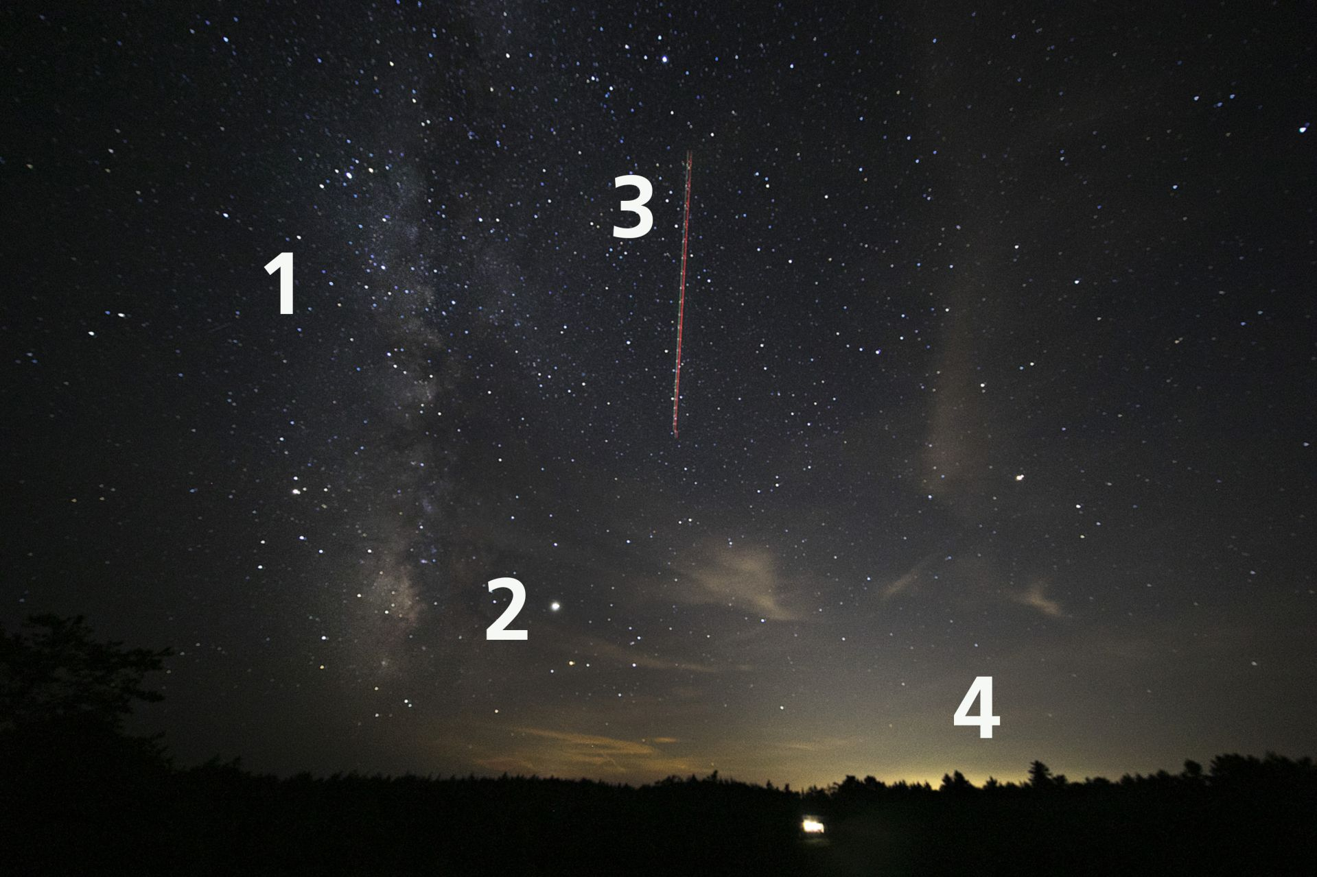 Four items In the night sky above the Coastal Center at Shortidge: (1) is the Milky Way, (2) is Jupiter, (3) is the trail of a passenger jet with red dots indicating its flashing beacon, and (4) is light from the city of Portland, made prominent by the long image exposure. (Theophil Syslo/Bates College)