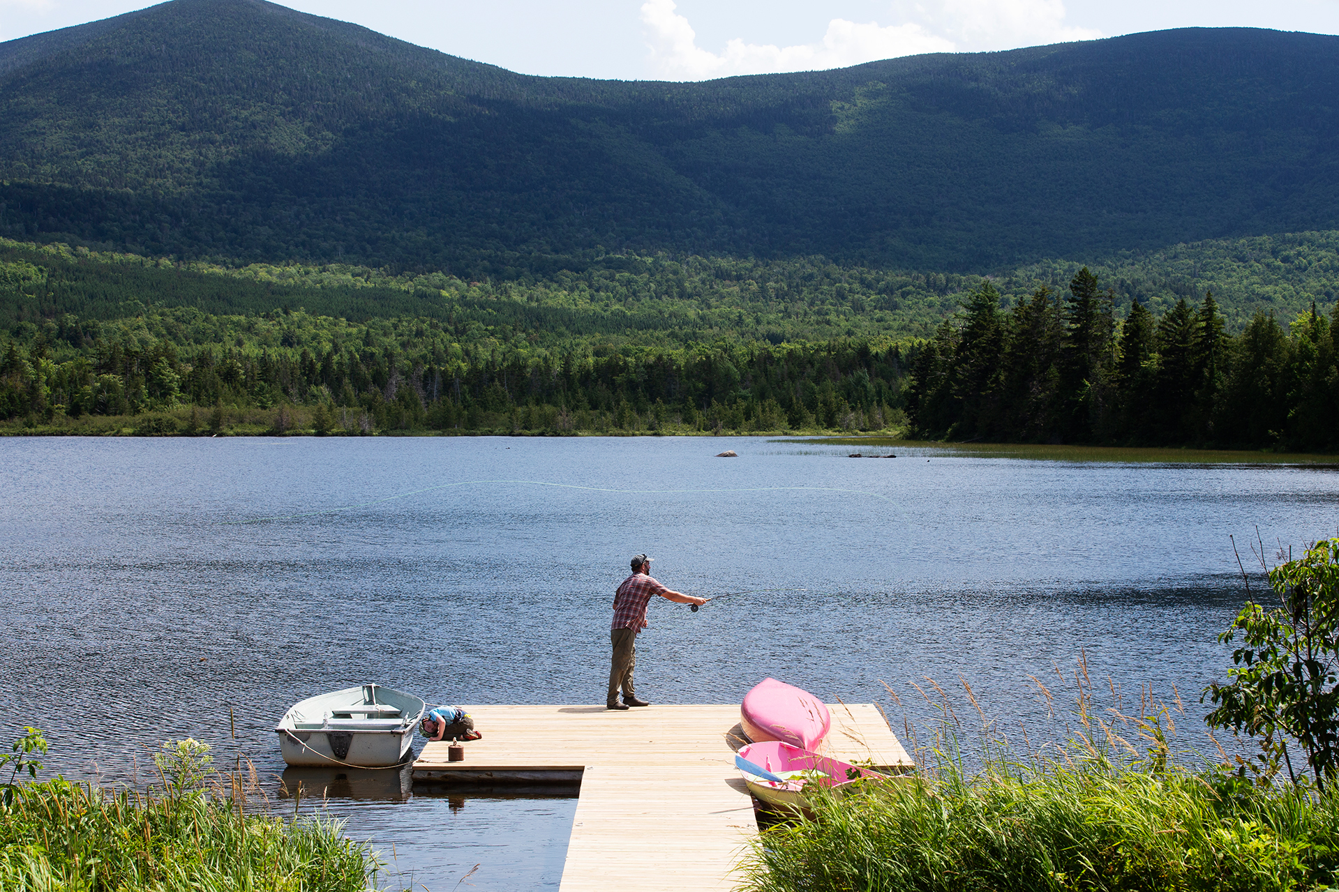 With White Cap Mountain impressive in the distance, Eric Stirling '97 casts from the dock at West Branch Pond Camps in early August. (Theophil Syslo/Bates College)