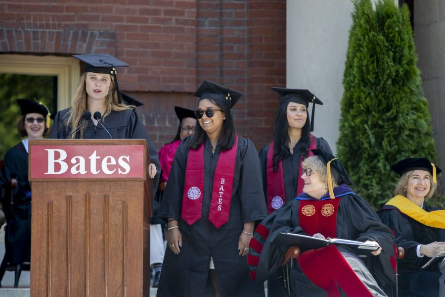 Senior Gift co-chair Erika Lamere '19 speaks to the Commencement audience, joined on the platform by co-chairs Elizah Laurenceau '19 and Taylor Lough '19. Seated are President Clayton Spencer and Commencement speaker Jennifer Doudna. (Phyllis Graber Jensen/Bates College)