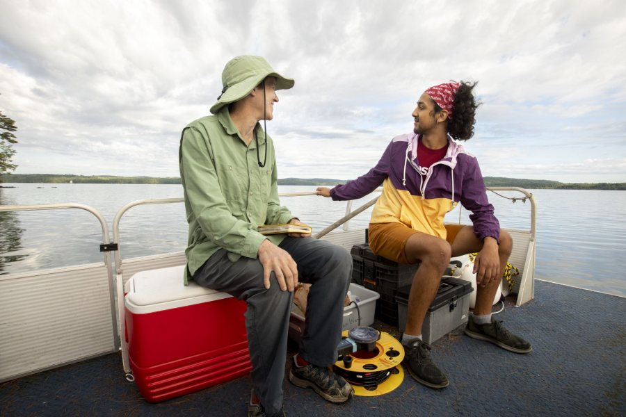 Topher Castaneda '20 (right) sits on a boat with Holly Ewing, Christian A. Johnson Professor of Interdisciplinary Studies, as they do fieldwork on Lake Auburn. (Phyllis Graber Jensen/Bates College)