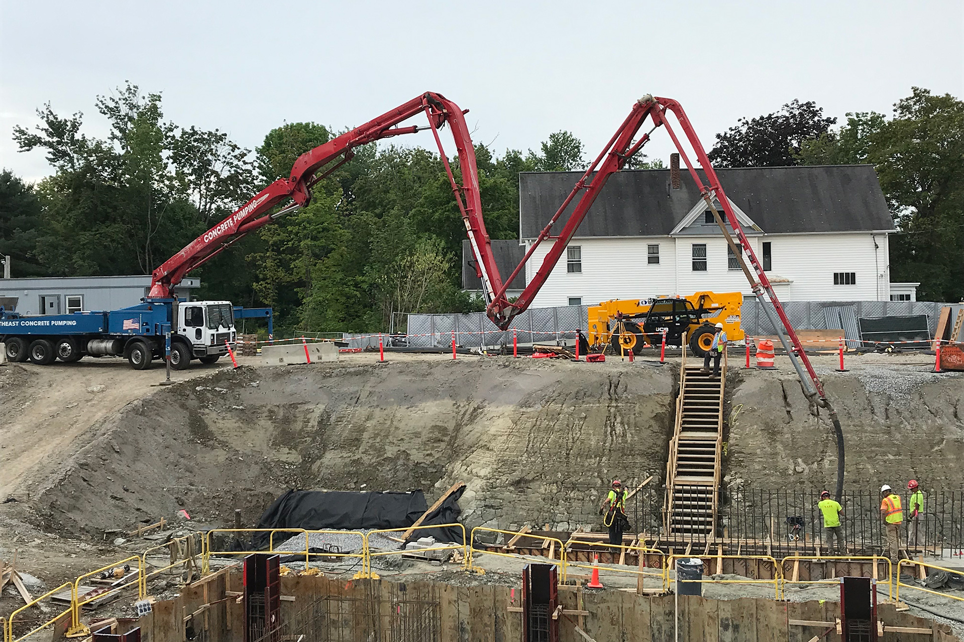 Dial M for concrete: Pumping concrete into a foundation footing on the south side of the Bonney Science Center on Aug. 21, 2019. (Doug Hubley/Bates College)