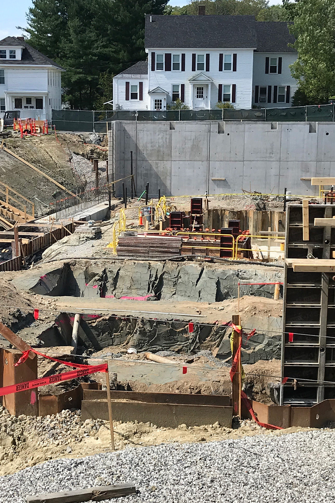 "Shown, from rear, are a foundation wall at Nichols Street; the ""cofferdam""; at left, a foundation footing; two pits that will hold additional footings; at right, a section of a wall form. (Doug Hubley/Bates College)"
