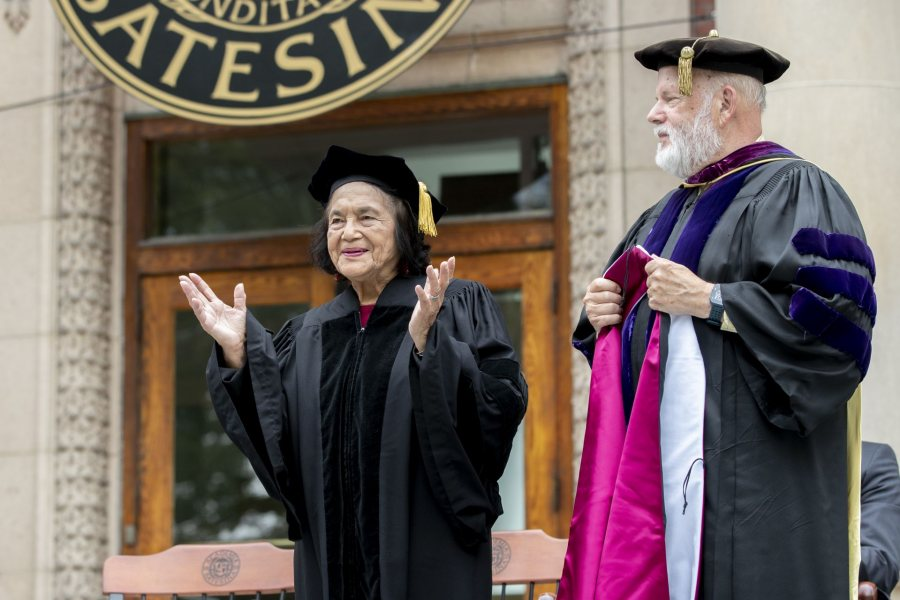 Dolores Huerta acknowledges applause as she's given an honorary degree at Opening Convocation. Ready to present her with the honorary hood is Michael Murray, Phillips Professor of Economics. (Phyllis Graber Jensen/Bates College)