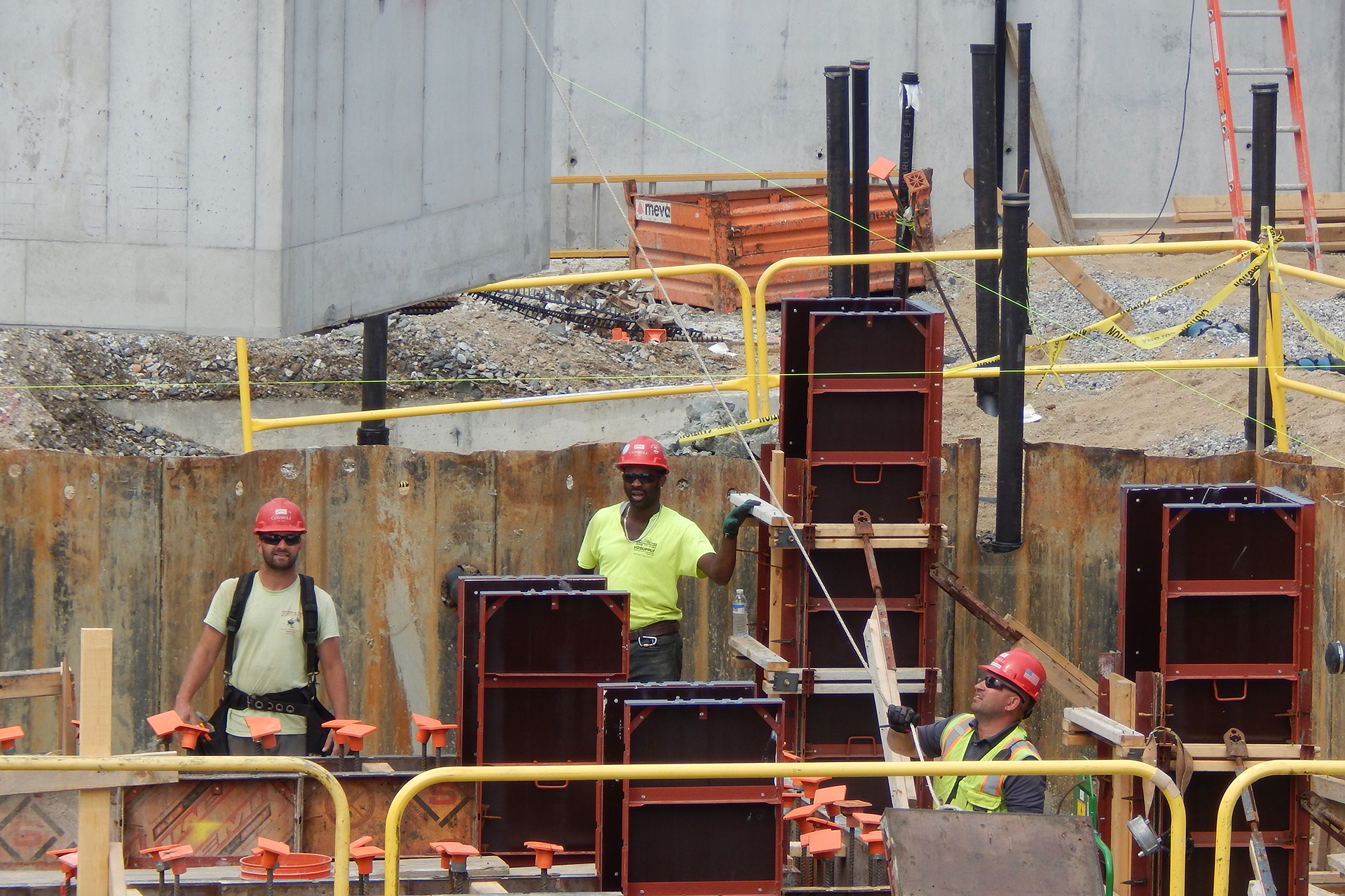 At upper left, a precast concrete holding tank is being lowered into the Bonney Science Center foundation while the worker at lower right pulls on a rope to guide it. The tank will store waste liquids. The red-and-black objects are forms for concrete columns. (Doug Hubley/Bates College)