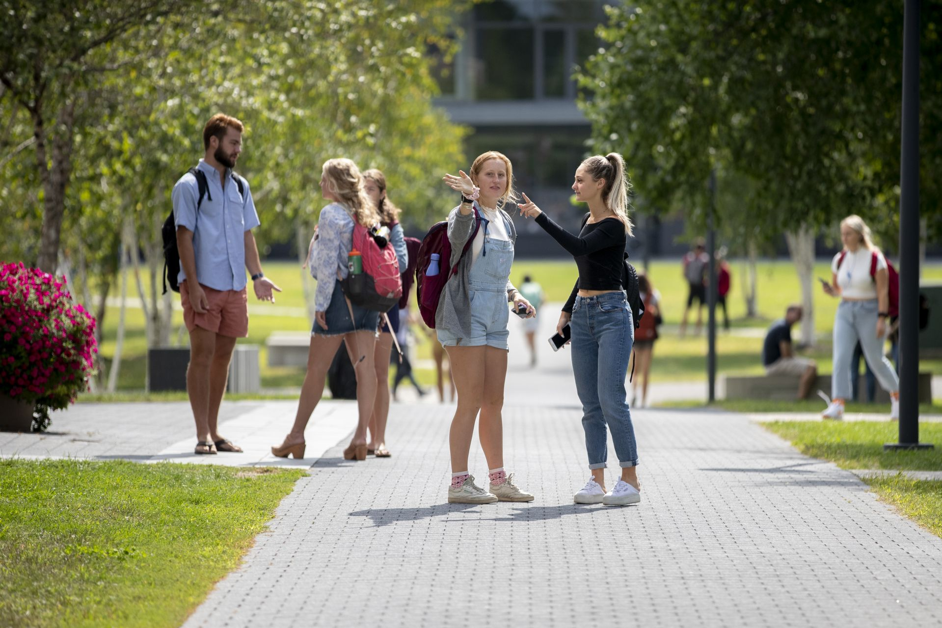 . On the first day of classes Daphne James '22 of Sausalito, Calif., greets classmates Anna Rozin of Ontario, Canada — and reminds her where Pettigrew Hall, the location of her next class, is. (Phyllis Graber Jensen/Bates College)