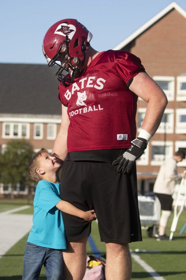 Captain CourageousSix-year-old Brayden Austin gives a leg hug to Phil Simplicio '20 of West Hartford, Conn., during a football practice at Garcelon Field in September.