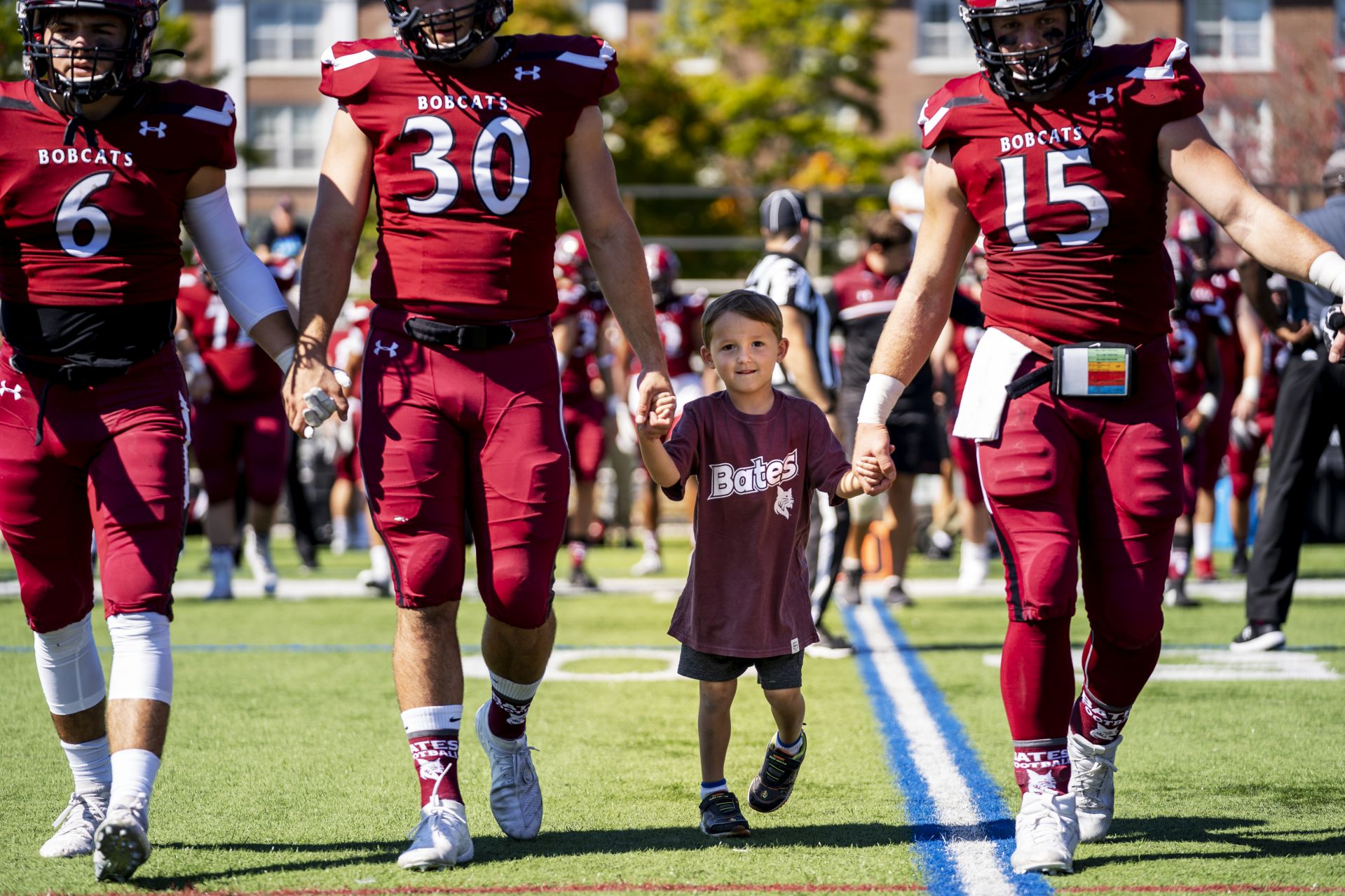 Brayden Austin walks onto Garcelon Field for the coin toss vs. Middlebury on Sept. 21 with seniors Jon Lindgren of Plainville, Conn., Zach Doyon of Eliot, Maine, and Matt Golden of New Bedford, Mass. (Theophil Syslo/Bates College)