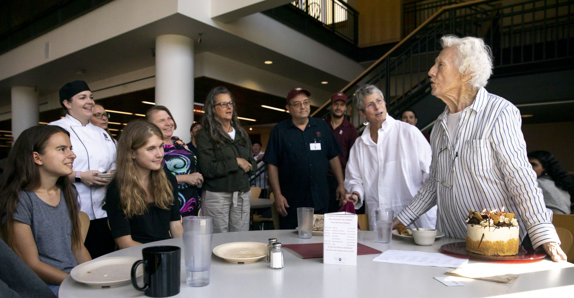 """After a 100th birthday cake — baked and delivered by Dining Services — arrived at her table, Dorothy Foster Kern '42 rises to thank everyone for her birthday lunch at Commons. """"Thank you so much,"""" she said. """"I am so proud to have gone to Bates!"""" Also joining the lunch were students Vanessa Paolella '21 (seated, left) and Abby Hamilton '21 (next to Paolella) and James Jones '20, not pictured."""