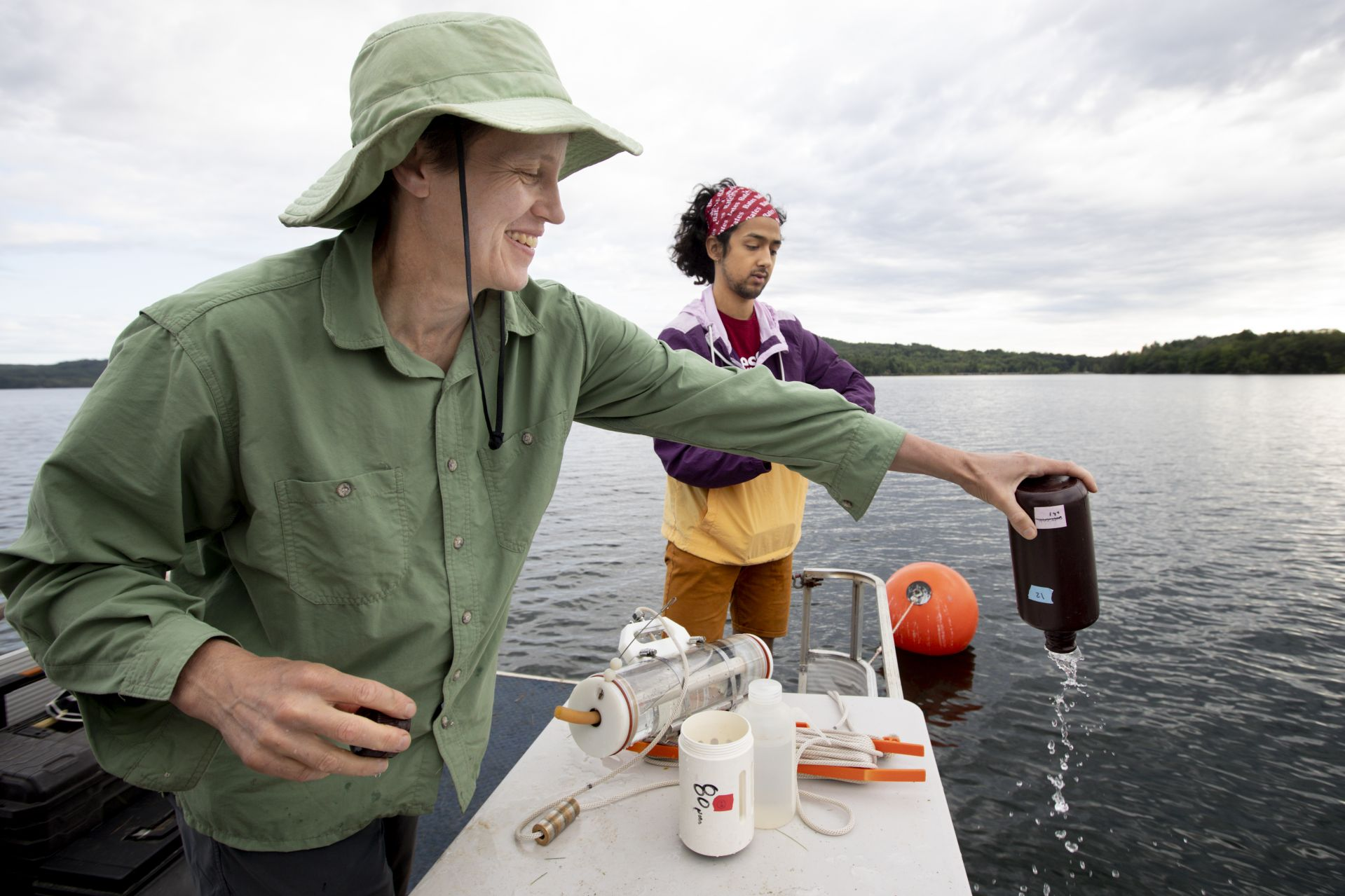 Professor of Environmental Studies Holly Ewing (left) and environmental studies major Christopher Castaneda '20 take water samples from Lake Auburn on Aug. 15, 2019. Ewing is central to a five-state effort, supported by a $5.9 million National Science Foundation grant, to use high technology to better predict cyanobacterial blooms in lakes. (Phyllis Graber Jensen/Bates College)