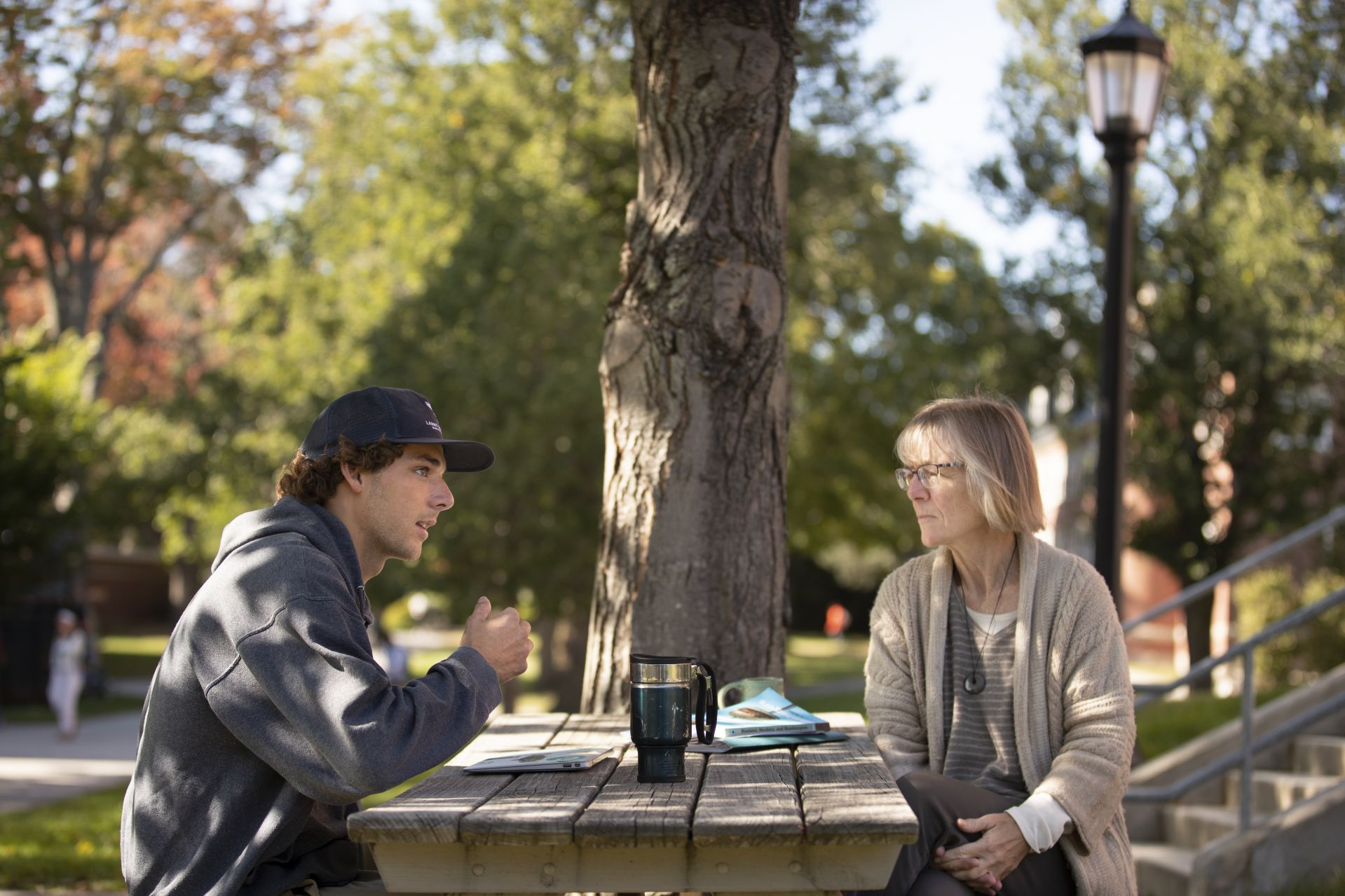 """""""You can just tell that she appreciates life and nature by the way she teaches,"""" says Lars Schuster '20, an environmental studies major from Simsbury, Conn., meeting with Costlow outside Roger Williams Hall to discuss his senior thesis. (Phyllis Graber Jensen/Bates College)"""