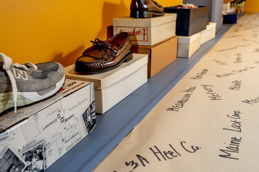 Brand and business names associated with the local shoe industry are handwritten on a long strip of paper, displayed with some of the shoes named. (Phyllis Graber Jensen/Bates College)
