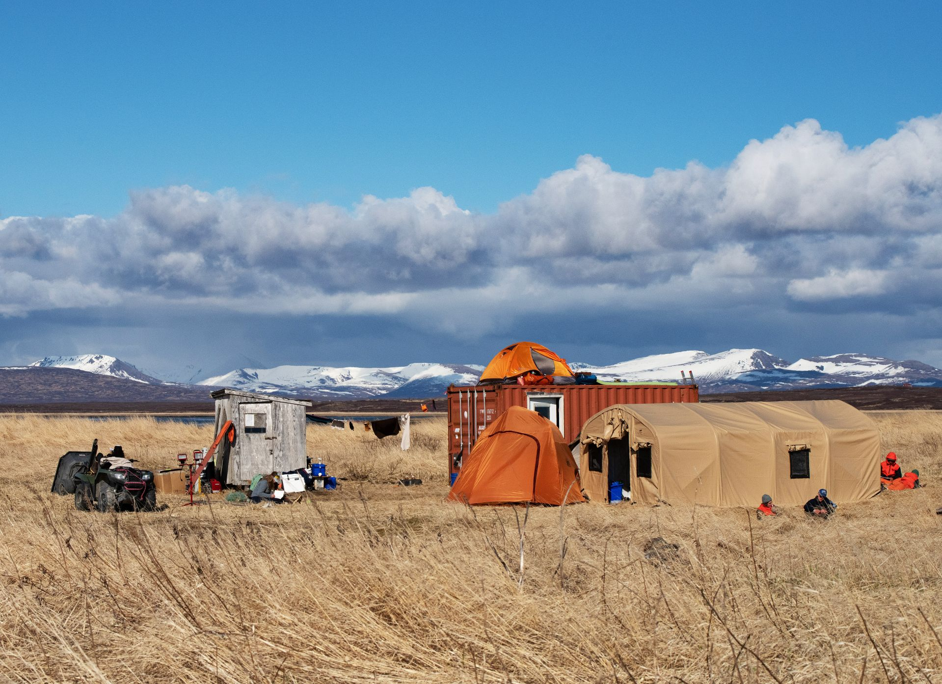 The campsite at the Old Togiak. From left, an ATV and cart; wooden shack used as the camp kitchen; the 10-by-20 shipping container fitted with six bunks; Barnett's tent atop the container; and another tent and WeatherPort nearby. (Tim Leach '99 for Bates College)