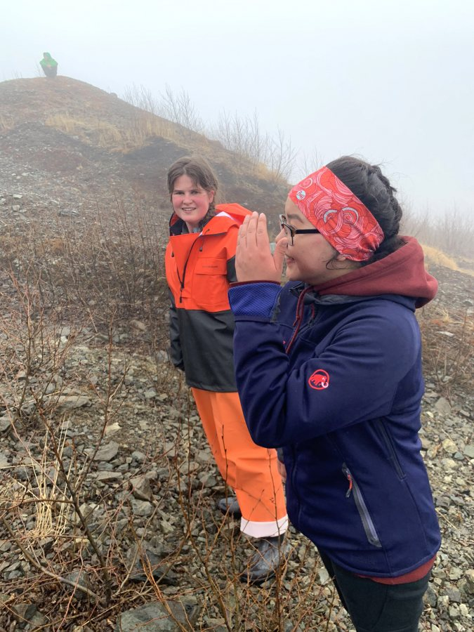 Anna Truman-Wyss '21 (left) and Skylar Wassillie, a student from Togiak School, walk together during the annual climb up Two Hill near the village. (Courtesy Kristen Barnett)