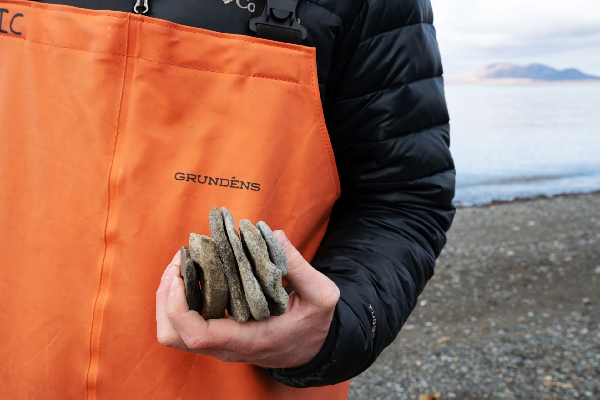 What L.L.Bean boots are to the campus, Grundéns outerwear was to students in Togiak. Near midnight on May 15, Ian Christiansen '22 holds rocks that he collected off the beach for skipping into Bristol Bay.(Tim Leach '99 for Bates College)