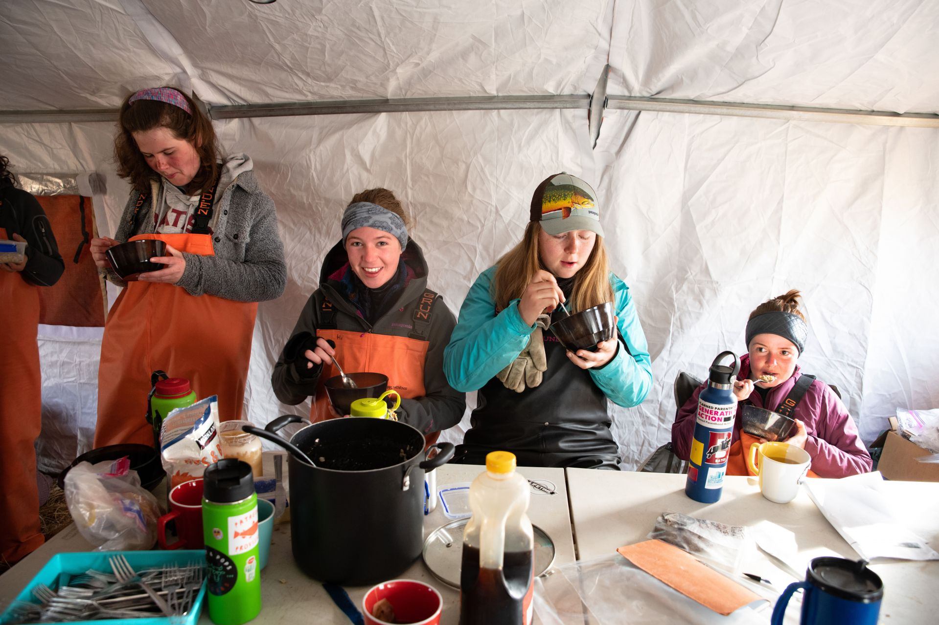 Having breakfast inside the camp WeatherPort are, from left, Anna Truman-Wyss '21, Hanna Webster '22, Emma Christman '22, and Solaine Carter '21. (Tim Leach '99 for Bates College)