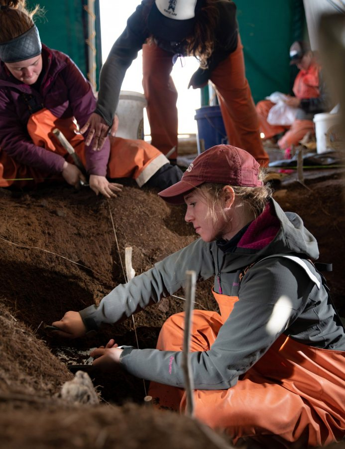 Trowel in hand, Hanna Webster '22 excavates soil at the Old Togiak site on May 15. (Tim Leach '99 for Bates College)