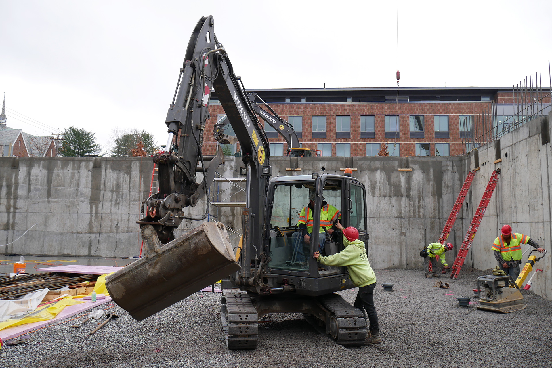 A scene in the Bonney Science Center basement: At center, an excavator operator and a colleague consult while a worker (far right) tends to his compactor and a steelworker (right rear) gathers his tools after working in the beam pocket at the top of the ladder. Chu Hall appears in the background. (Doug Hubley/Bates College)