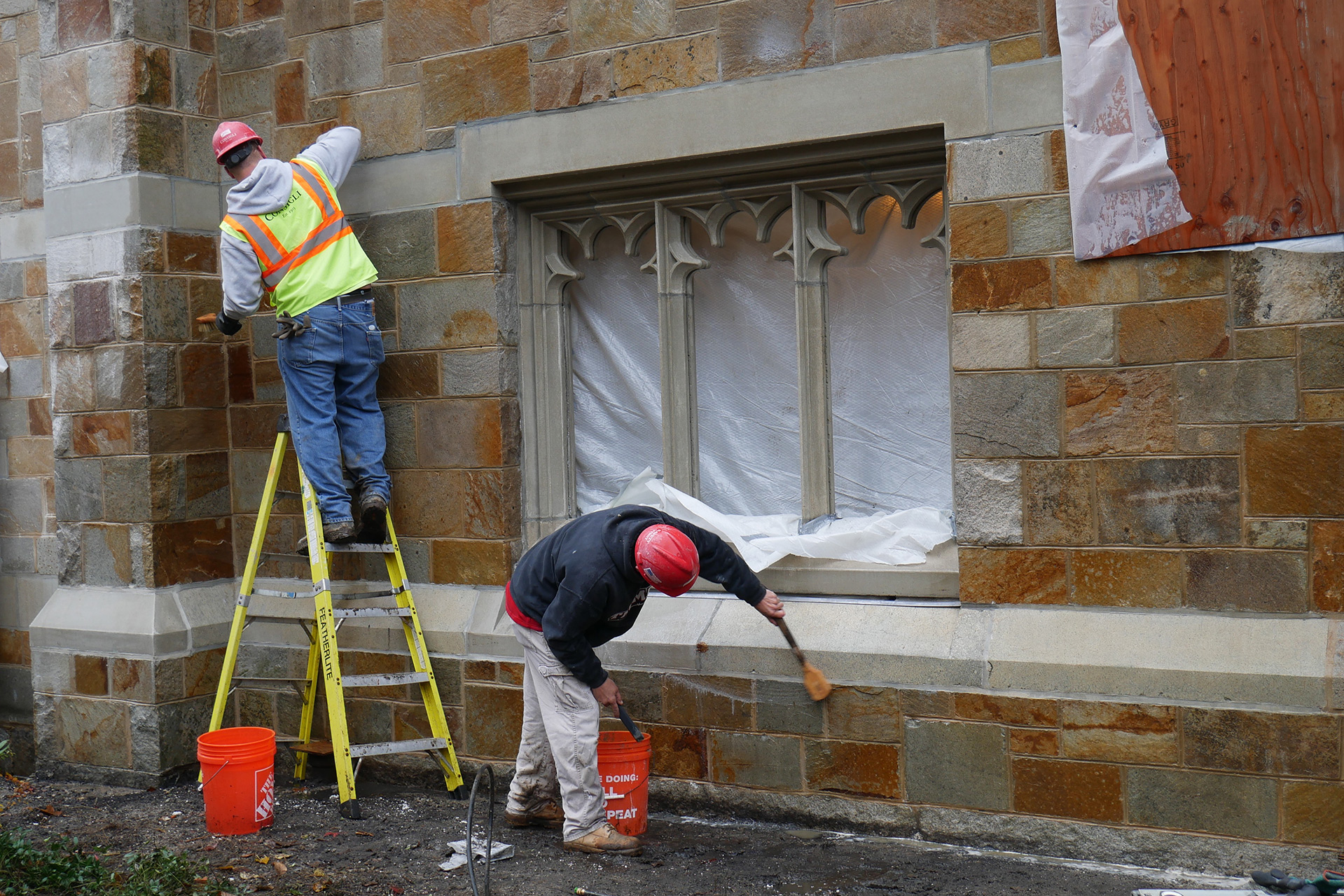 Cleaning up newly restored masonry on the east, or quad-facing, side of Gomes Chapel. All the masonry on this side has been repointed, and deteriorating pieces -- notably among the precast band courses -- have been repaired or replaced. (Doug Hubley/Bates College)