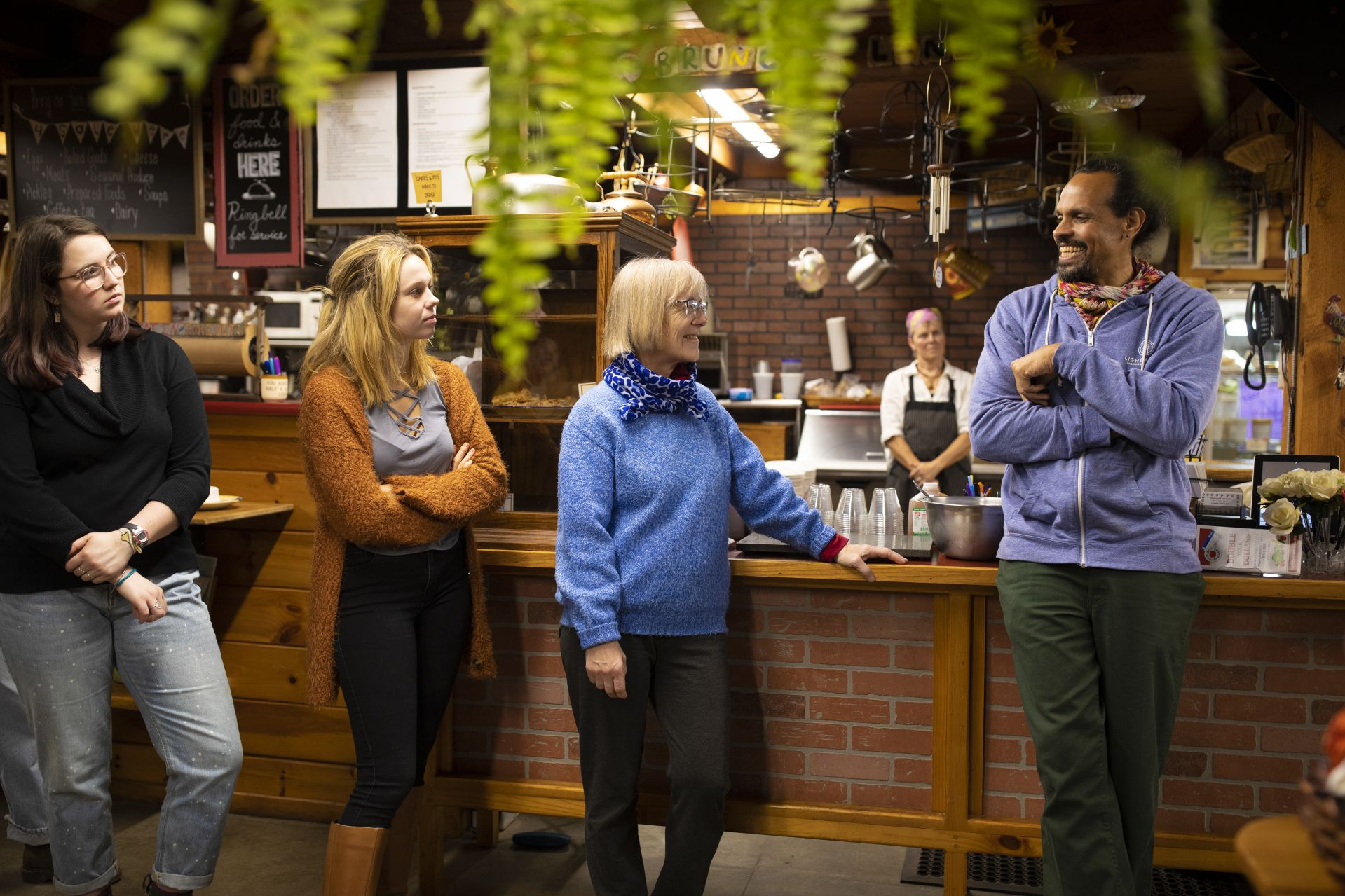 Before dinner at Nezinscot Farm, writer Ross Gay (right) speaks with Griffith Professor of Environmental Studies Jane Costlow (center) and environmental studies major Alexandra Cullen '20. (Phyllis Graber Jensen/Bates College)